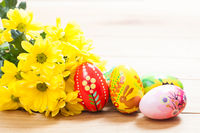 Colorful hand painted Easter eggs and spring flowers on wood