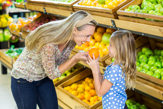 Mother and daughter holding orange