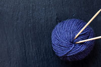 skein of purple yarn with bamboo knitting needles with black slate background