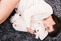 Young beautiful woman cuddling her Dog on the carpet