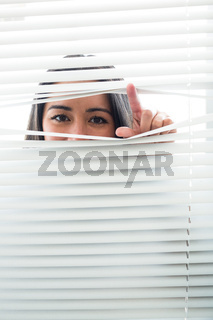 Woman peeking through some window blinds