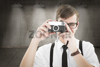 Composite image of geeky hipster holding a retro camera