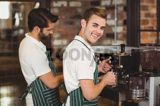 Two smiling baristas preparing coffee