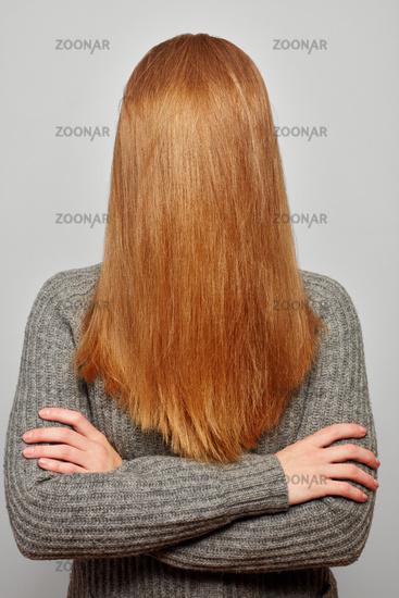 Frau hat lange blonde Haare vor Gesicht