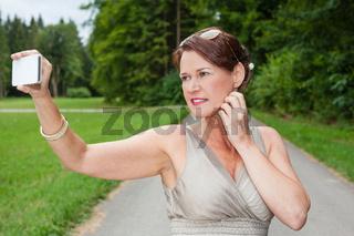 Frau im Kleid macht ein Selbstporträt mit Handy