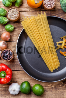 Various vegetables fruits and herbs with a frying pan on wooden background
