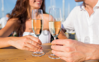 smiling couple clinking champagne glasses at cafe