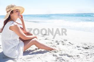 Brunette sitting in the sand and looking at the sea