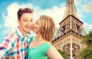 happy couple taking selfie over eiffel tower