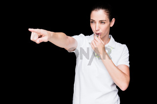 Female athlete blowing a whistle and pointing