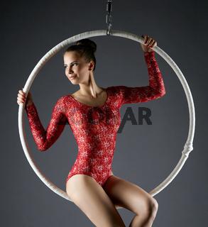 Portrait of lovely dancer posing on aerial hoop