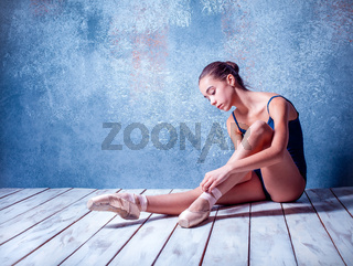 The young ballerina sitting on the wooden floor