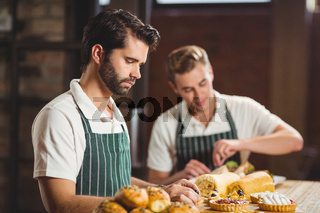 Concentrated waiters tidying up the pastries