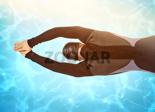 Composite image of rear view of swimmer in wetsuit while diving
