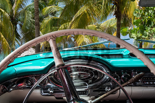Kuba Innenansicht eines mint farbenen Oldtimers mit Palmen und Blick auf das Meer