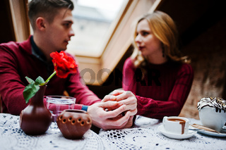 Hand of young beautiful stylish couple in a red dress in love story at the vintage cafe with big windows at the roof