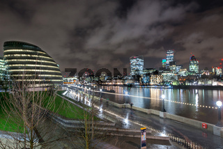 City Hall, London Assembly Building at night with City across River Thames, London, United Kingdom