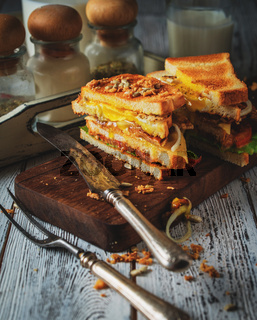 Sandwich with egg, tomato, onions and bacon on a vintage wooden background in rustic style