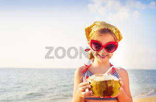 Happy adorable girl drinking coconut milk on the beach