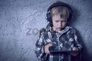 Boy listening music with headphones and tablet