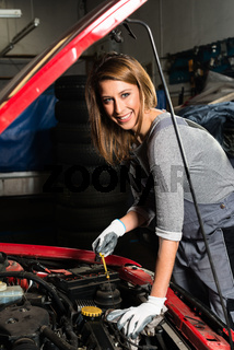 Young female trainee fixing car engine in garage