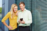 Zwei Geschäftsleute schauen auf Smartphone