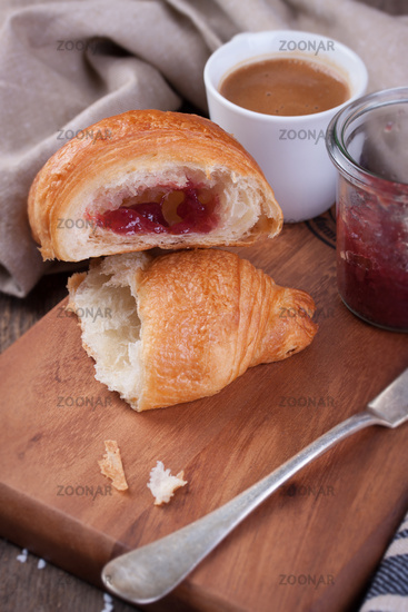 Closeup of croissant with jam and coffee on a wooden background