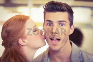 Portrait of shocked businessman being kissed