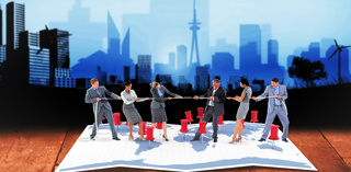 Composite image of business team pulling the rope