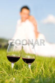two wineglasses with red wine in grass