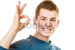 Young man showing ok hand sign gesture