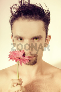 young man with gerberas in a hand
