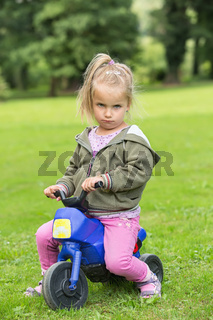 Frowning girl playing in the park on a motorbike