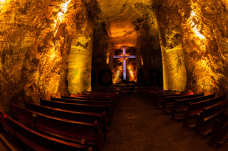 Underground salt cathedral Zipaquira main room with big cross and benches in blue light