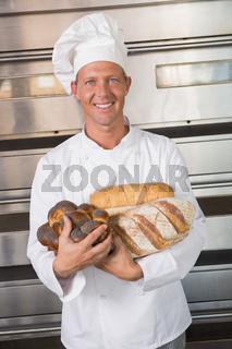 Smiling baker holding fresh loaves