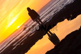 Woman on rocky beach watching sunset.