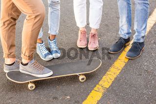 Lower section of hip friends and skateboard
