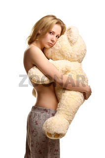 Girl in pijamas pants hugging giant plush bear