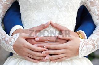 The groom gently hug the bride#39;s hands