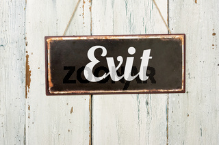 Old metal sign in front of a white wooden wall - Exit