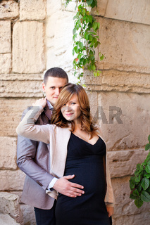 Man tenderly embraced Pregnant Woman