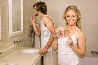 Blonde woman taking a pill with her boyfriend brushing his teeth