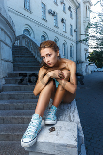 Beautiful girl in bodysuit posing with classical building at background