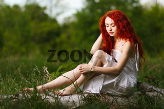 Redhead girl walking under rays of sunset forest