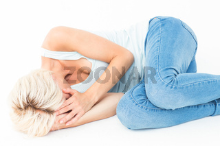 Sad blonde woman lying on the floor