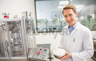 Happy pharmacist showing bowl of pills