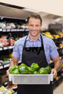 Portrait of a smiling handsome worker holding a box with vegetables