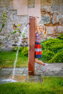 Little girl opens water tap