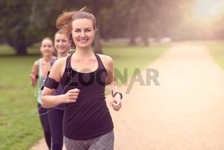 Hübsche Frau joggt im Park mit Freundinnen