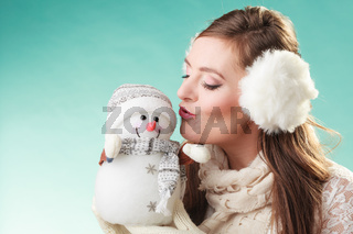 Cute woman kissing little snowman. Winter fashion.